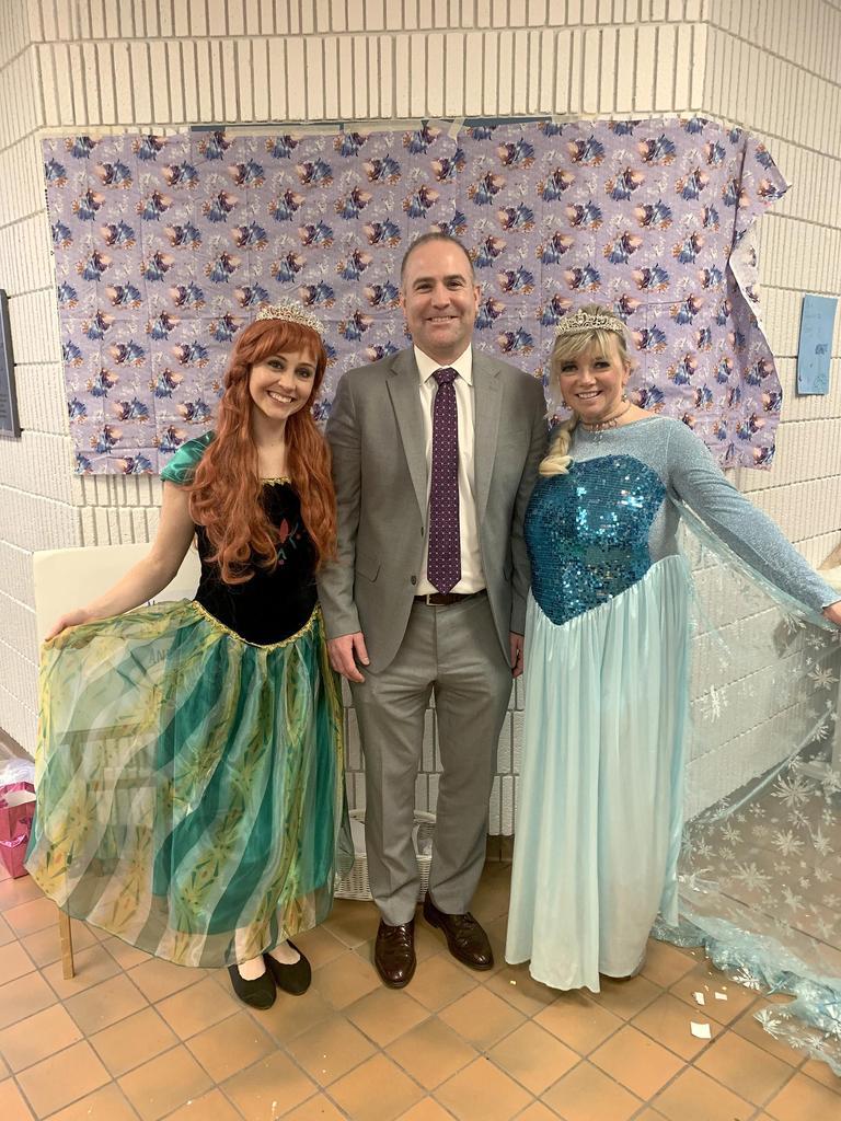 Principal Michael McLuas with two Disney princess characters