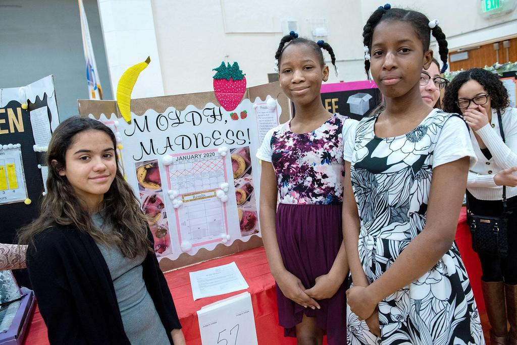 Three middle school students stand in front of their project