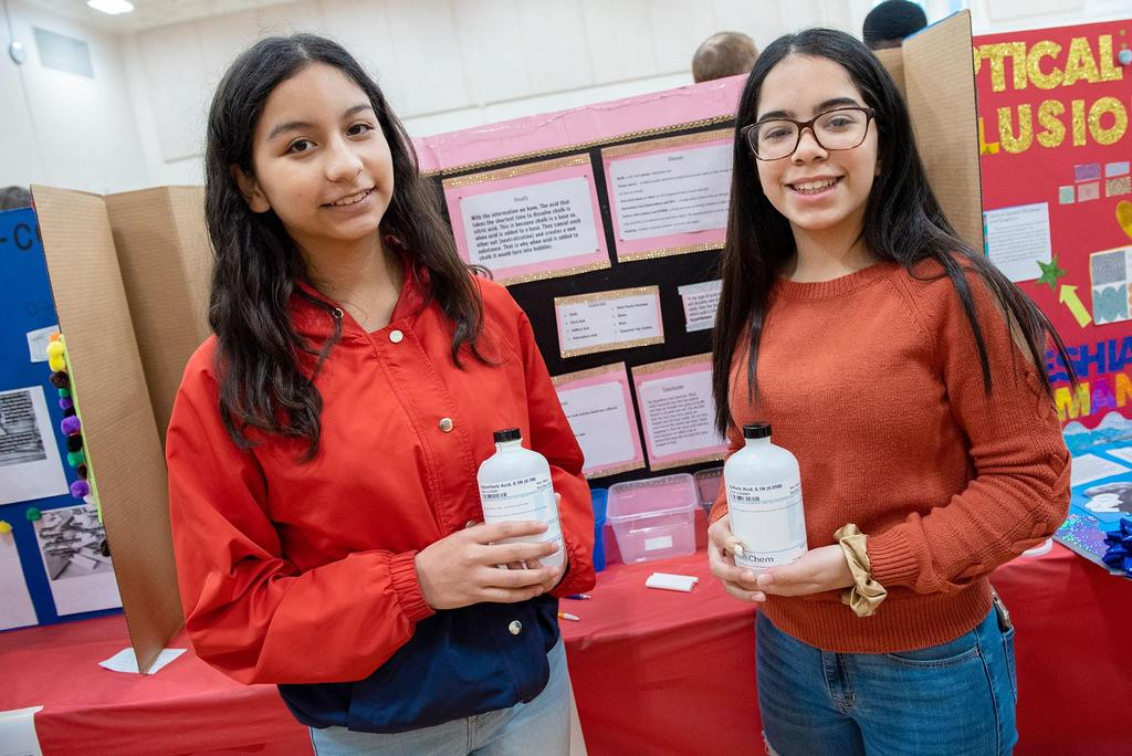 Two students hold containers of liquid as they stand in front of their project