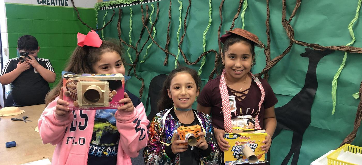 3 girls posing with cameras they made from recycled paper products