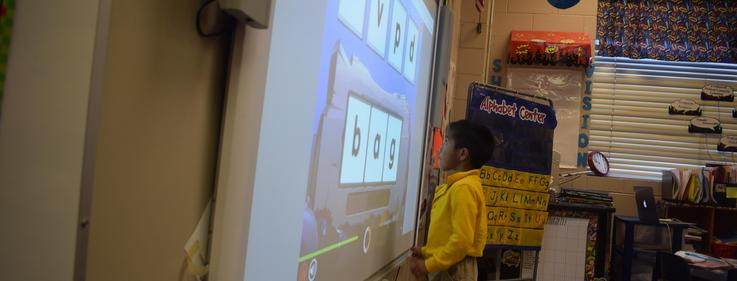 Student working on smart board.