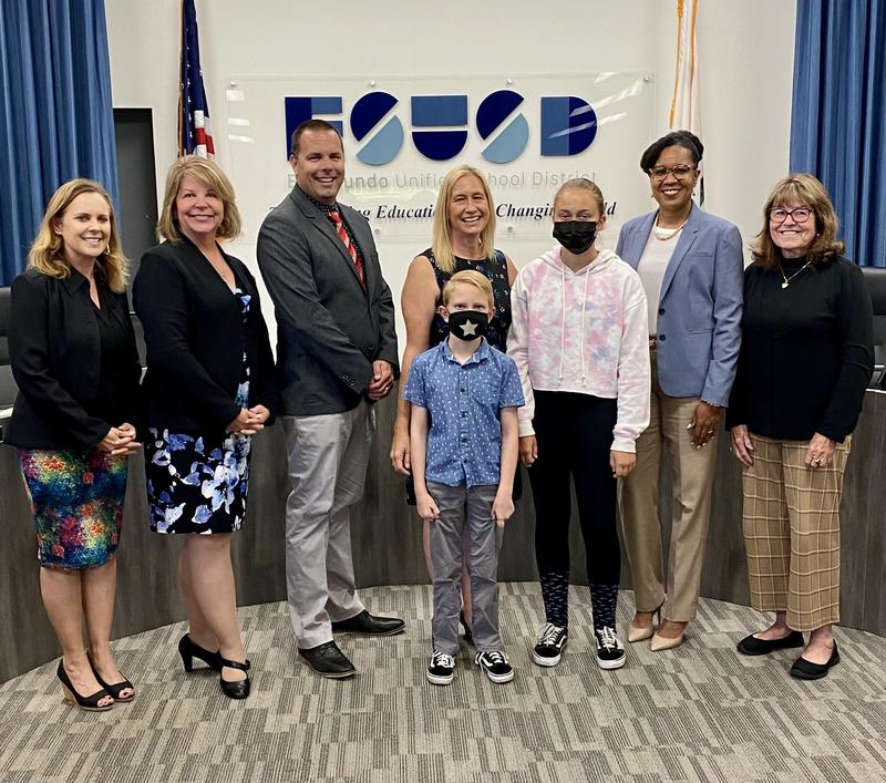 Newly hired Assistant Principal Bridget Fredrickson with family, Principal Wright, Dr. Moore, and the Board of Education.