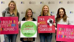 Four women holding signs relating to school counselors.