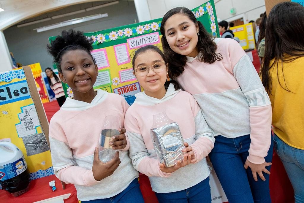 Three students, two holding plastic containers
