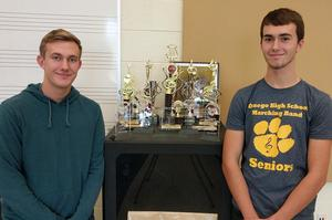 Drum majors Robby Kalleward and Sam Herbert stand with the band's trophies.