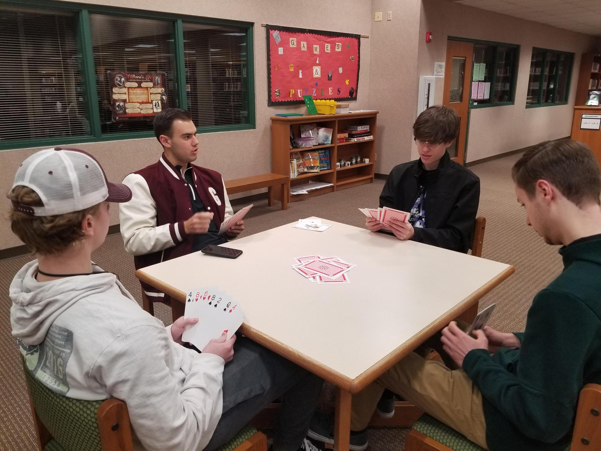 Four male students play cards together at a table