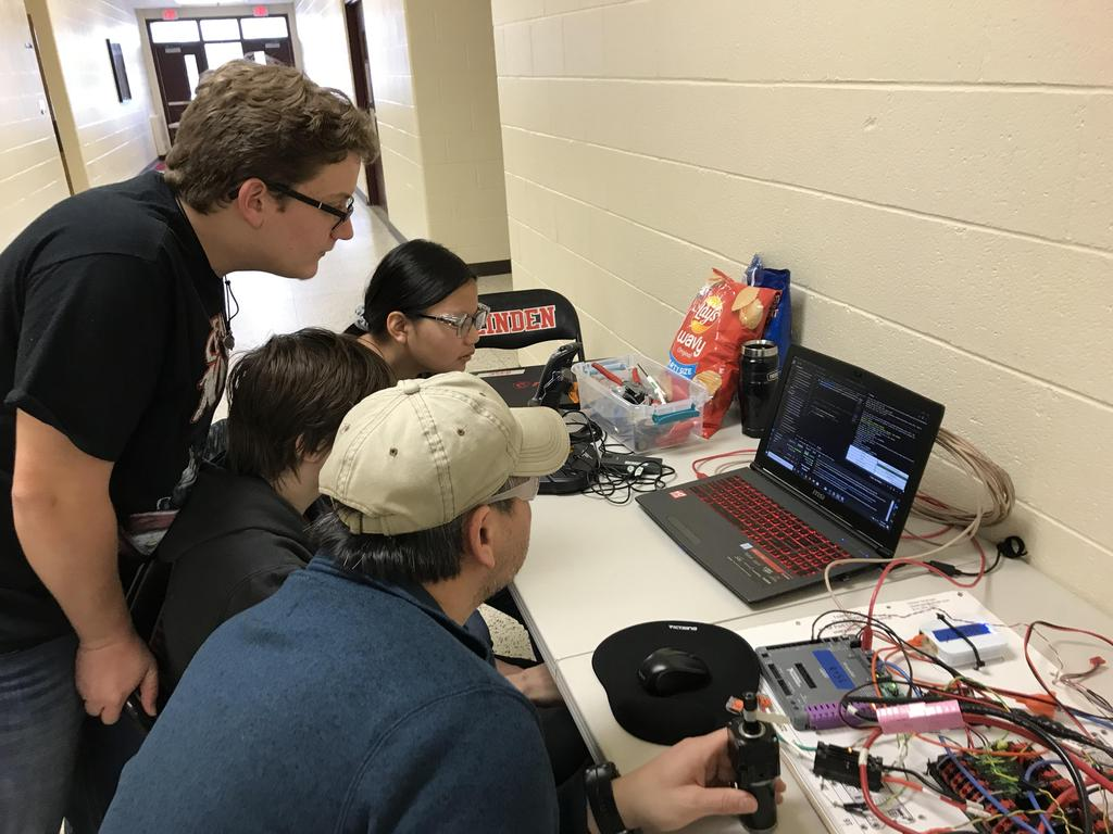 Four students looking at a computer screen