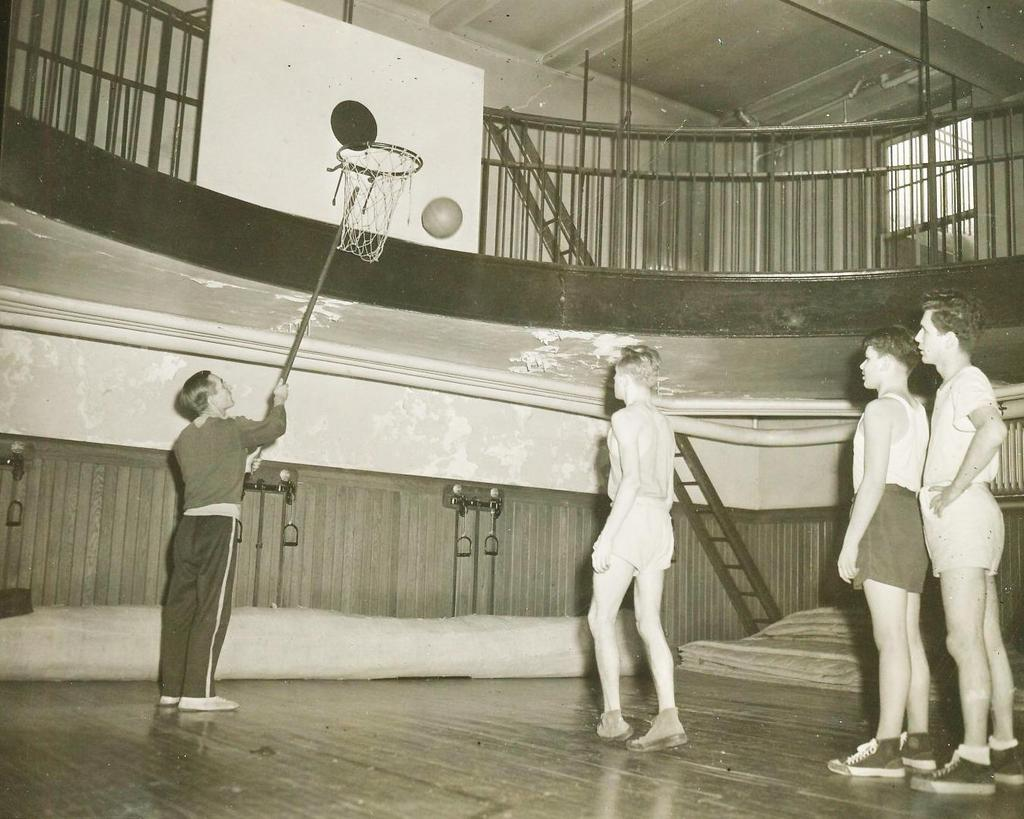 Students shooting a basketball at hoop as instructor taps the rim with a stick