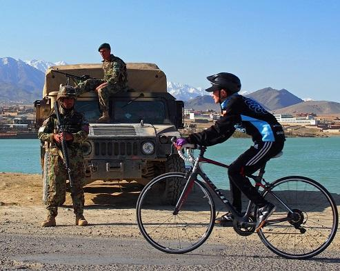 Shannon Galpin cycling past Afghan Army soldiers