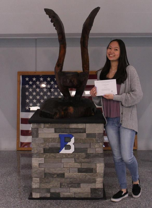 BHS Senior Julia posed next to a large, brown wooden owl, holding her certificate.l