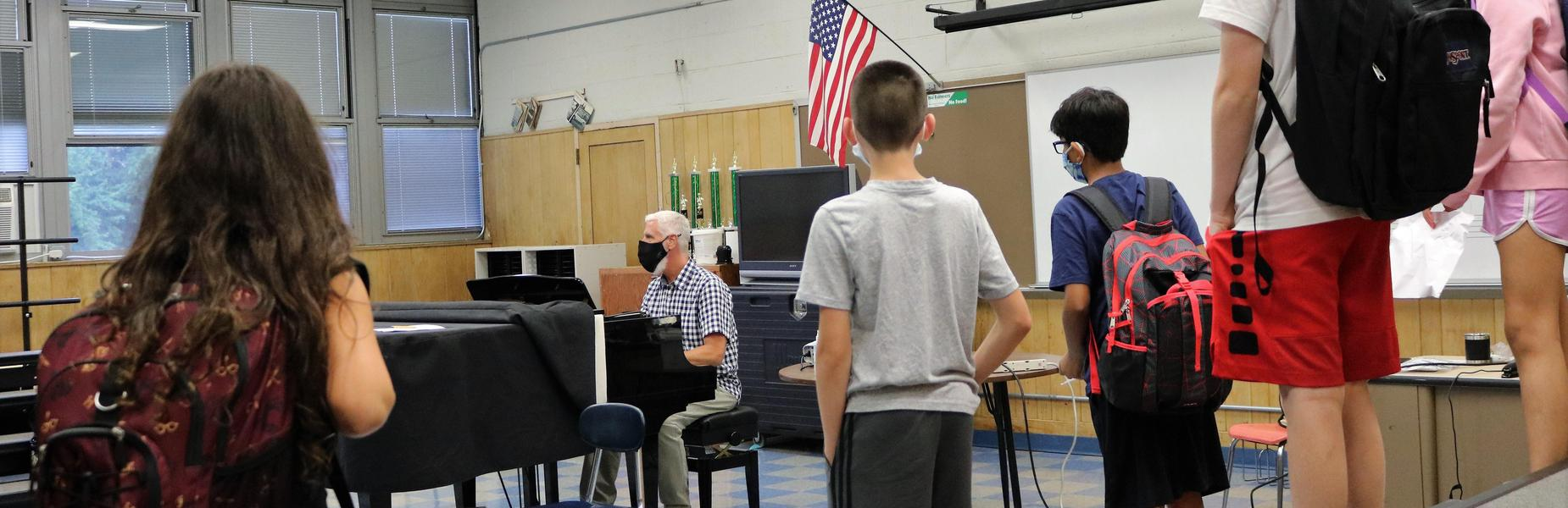 Photo of music teacher on piano with students singing, wearing masks.