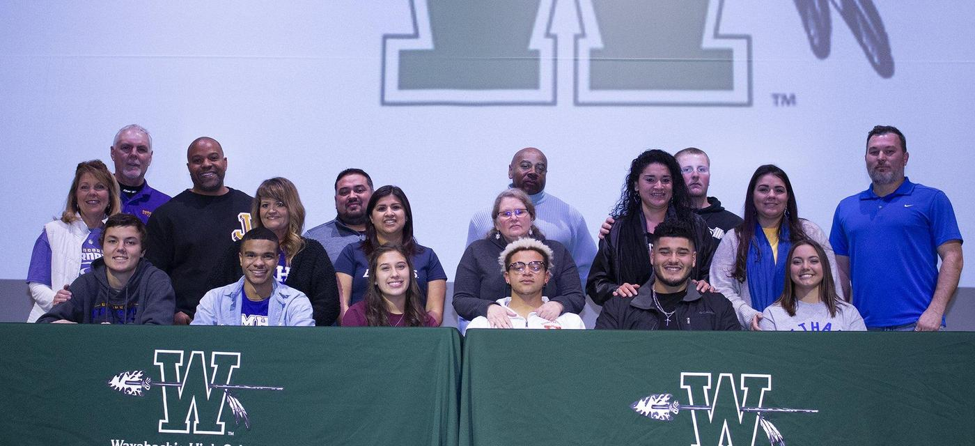 6 students pose with their families on signing day