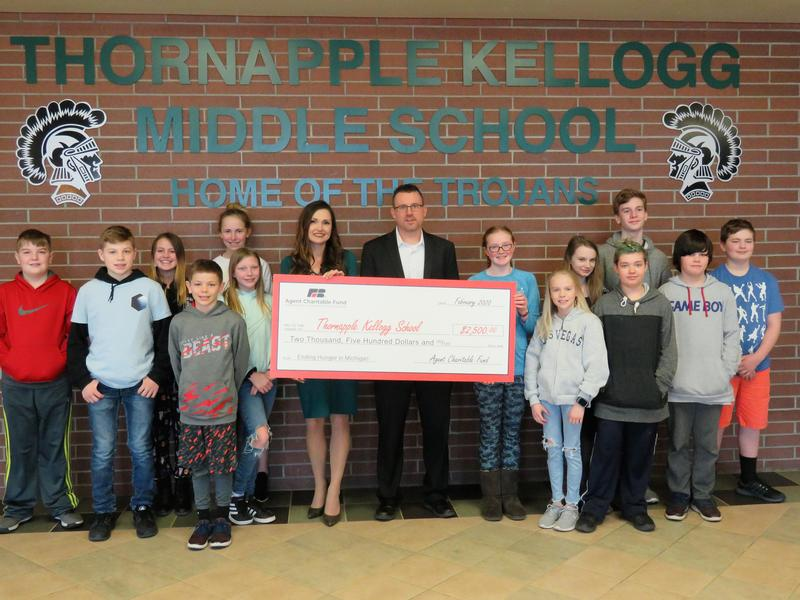 Jason Parks Farm Bureau Insurance Agency of Middleville presents a grant check to TK Food Service Director Jessica Endres and TKMS garden club students.