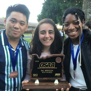 three teens holding trophy