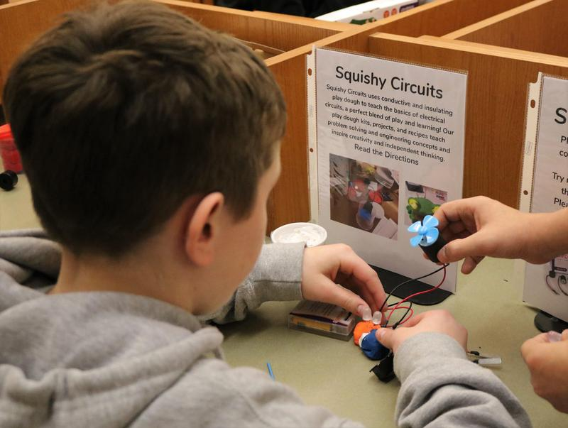 """Photo of:  A 7th grade student at Roosevelt Intermediate School tries his hand at """"Squishy Circuits"""" to learn the basics about electrical circuits during """"Maker Day"""" on March 21."""