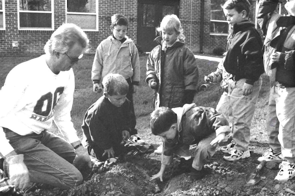 Planting flowers in honor of Monsignor.