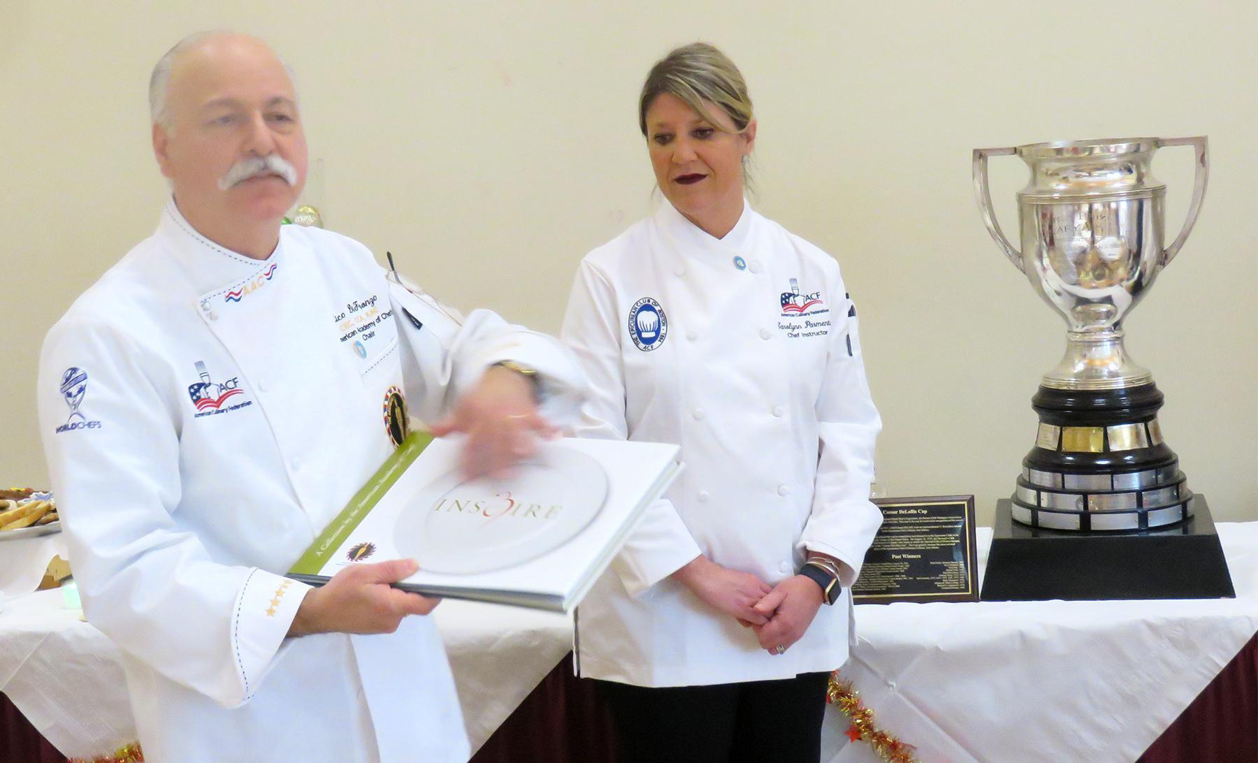 Epicurean Club of Boston Financial Secretary Americo S. DiFronzo presents a book to EHS Culinary Arts Director Carolynn Parmenter