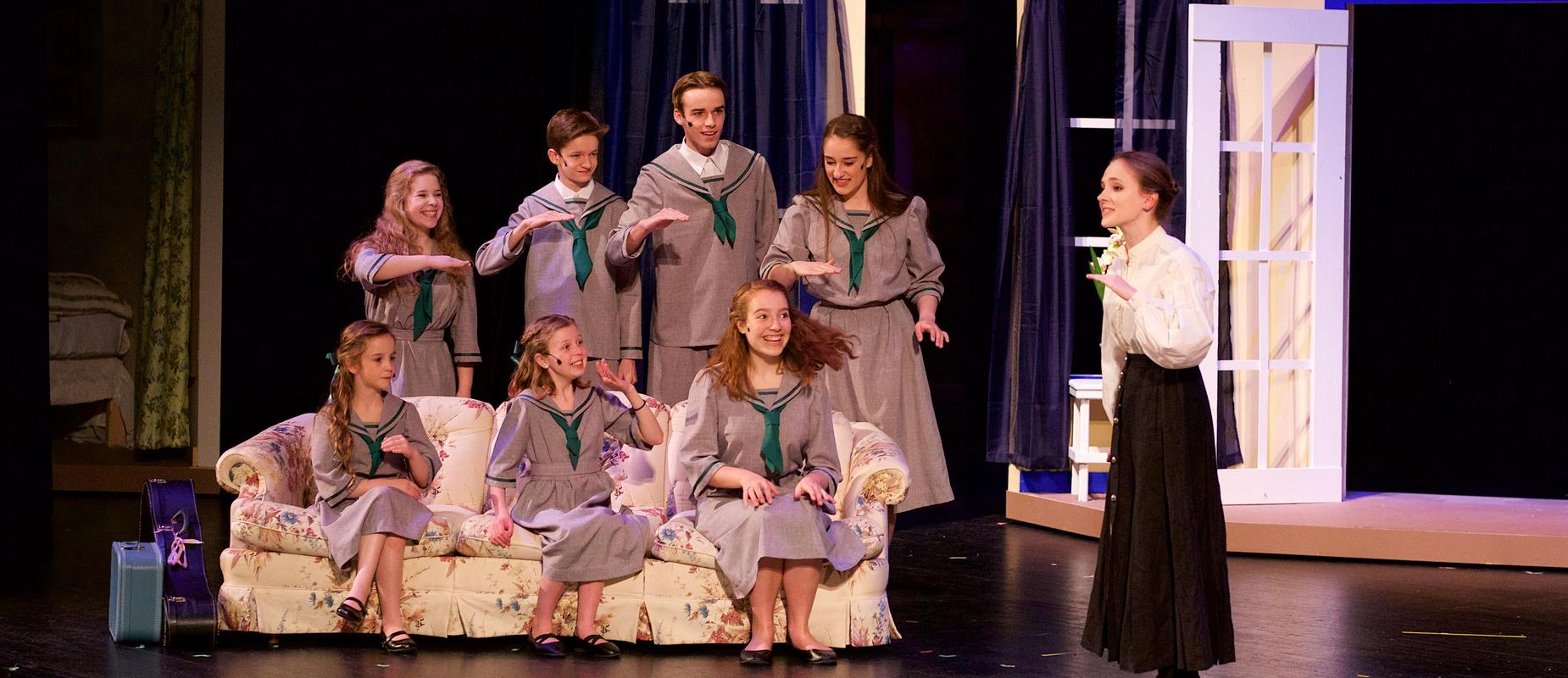 The Sound of Music children sing on couch in musical stage