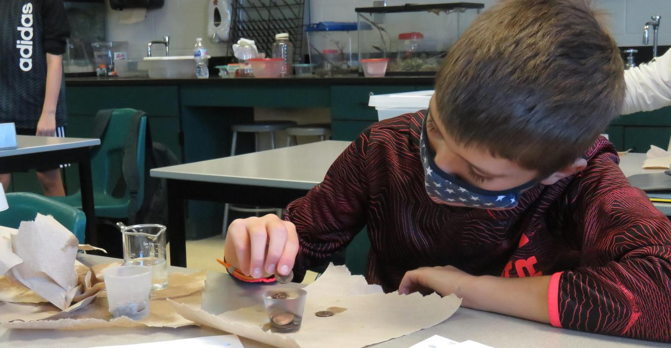 A  Middle School student keeps a steady hand as he conducts a science experiment.