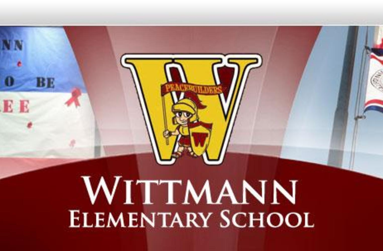 Photo of Wittmann Logo, a Drug Free Poster, and flags in front of the school