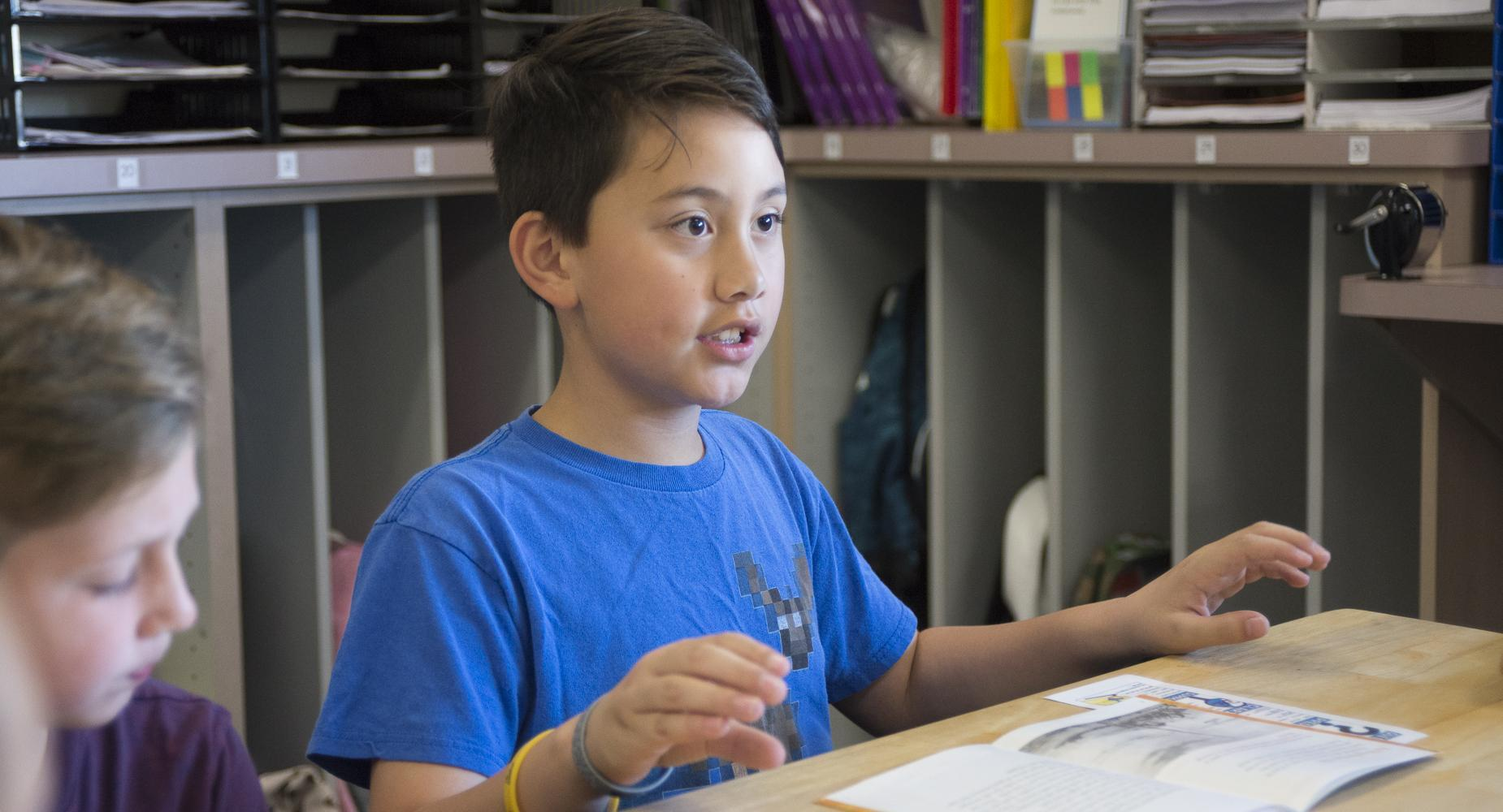 Boy talks with book laid out on desk