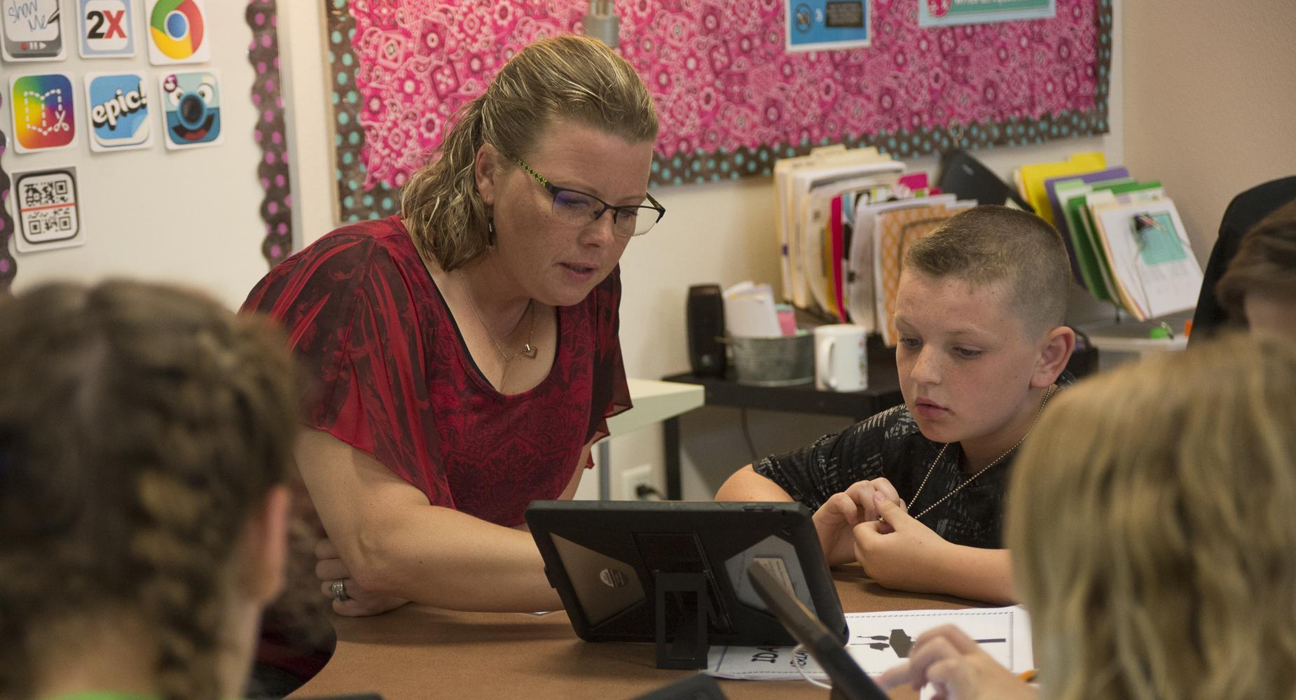 Teacher assists boy with his iPad