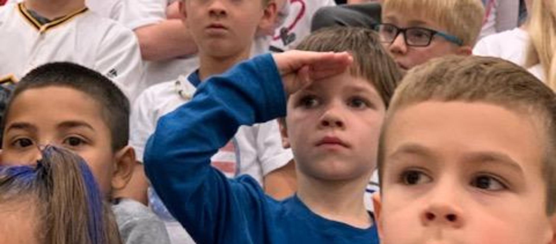 student saluting veterans
