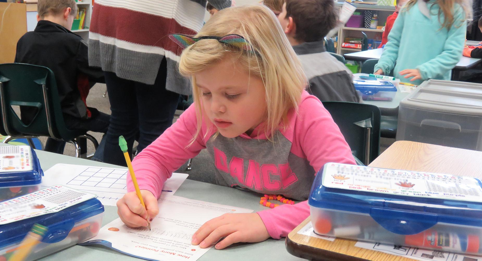 Girl in pink shirt works on worksheet at her desk.