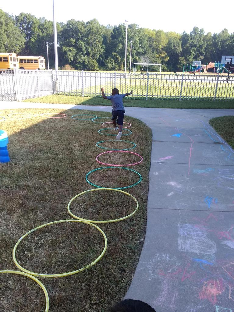 Pre-K student playing hop scotch outside of school using hool-a-hoops.