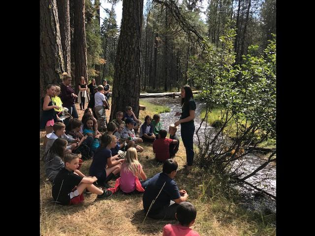 Fourth Grade teacher Mrs. Crowther speaks to attentive children in a riparian setting-- next to a creek.