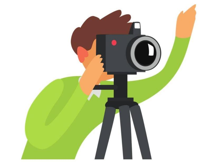 Man in green shirt taking a photo with a professional camera. One hand is holding the camera and the other hand is waving in the air.