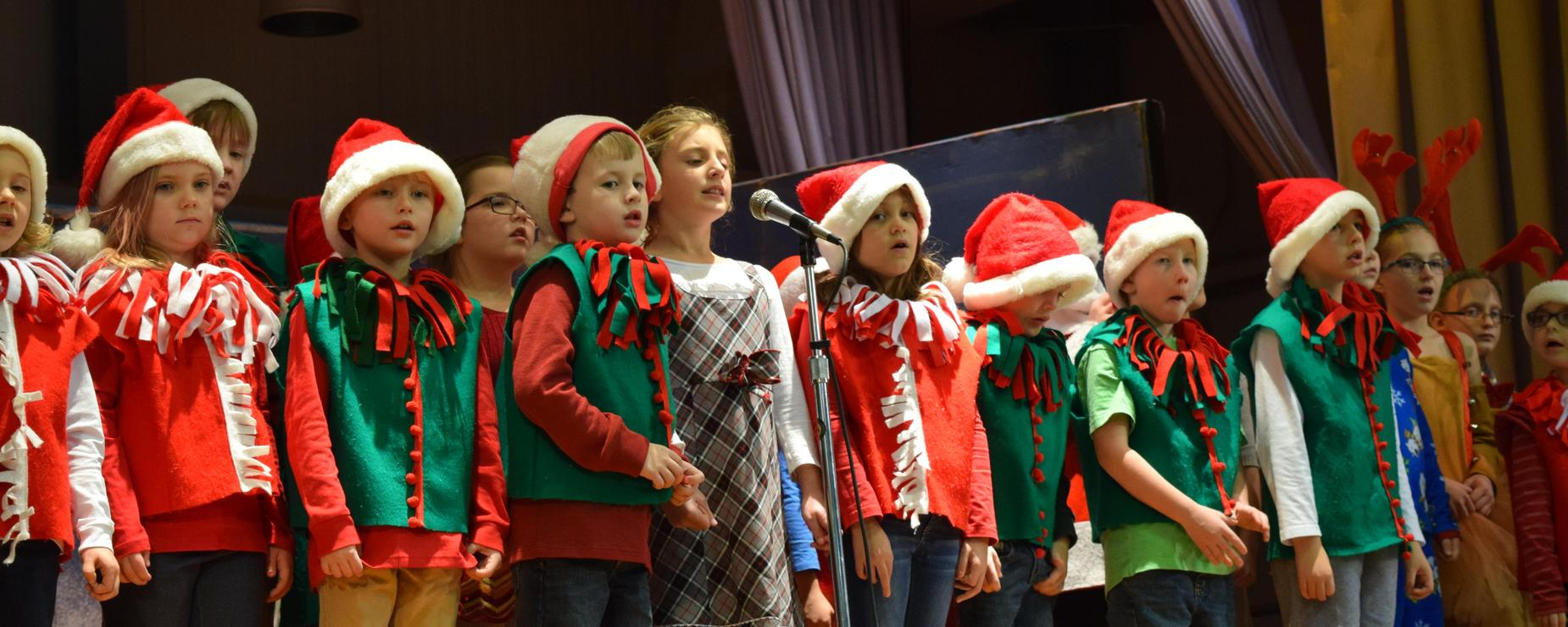 Elementary students dressed in elf costumes perform for their Winter concerts