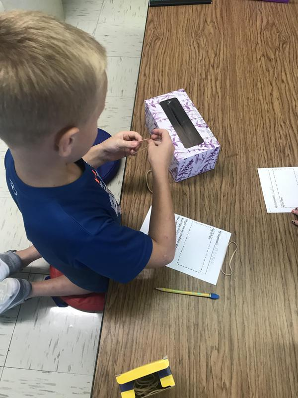 A student experiments with sound using a tissue box.