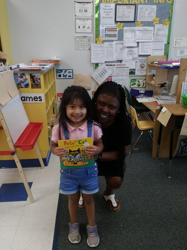 Mrs. Bunch with Pre-K Student holding book Pete the Cat