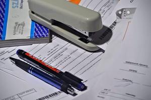 Paperwork and pens and a grey stapler