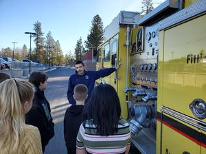 Firefighter showing the fire truck to students