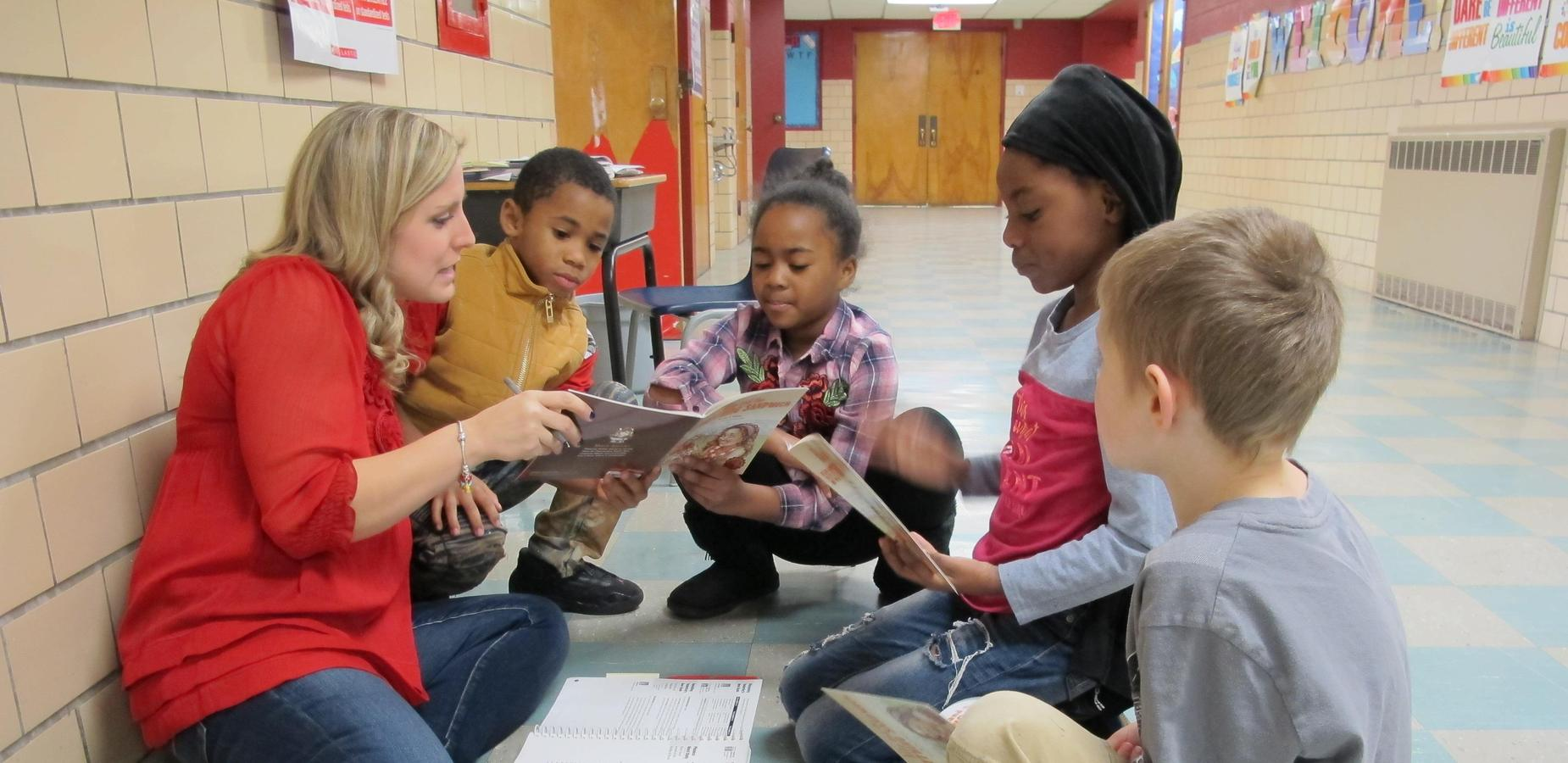 Teacher working with a reading circle of students.