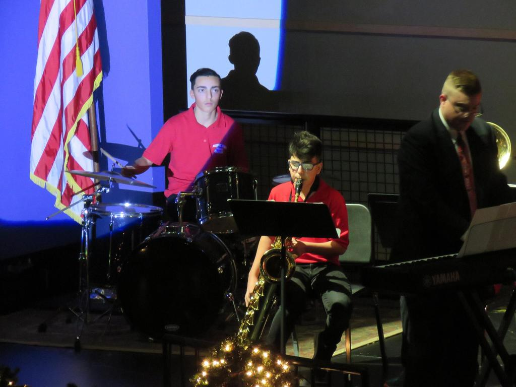 A drummer, a sax player, and a teacher playing the keyboard against a shadowy backdrop on stage