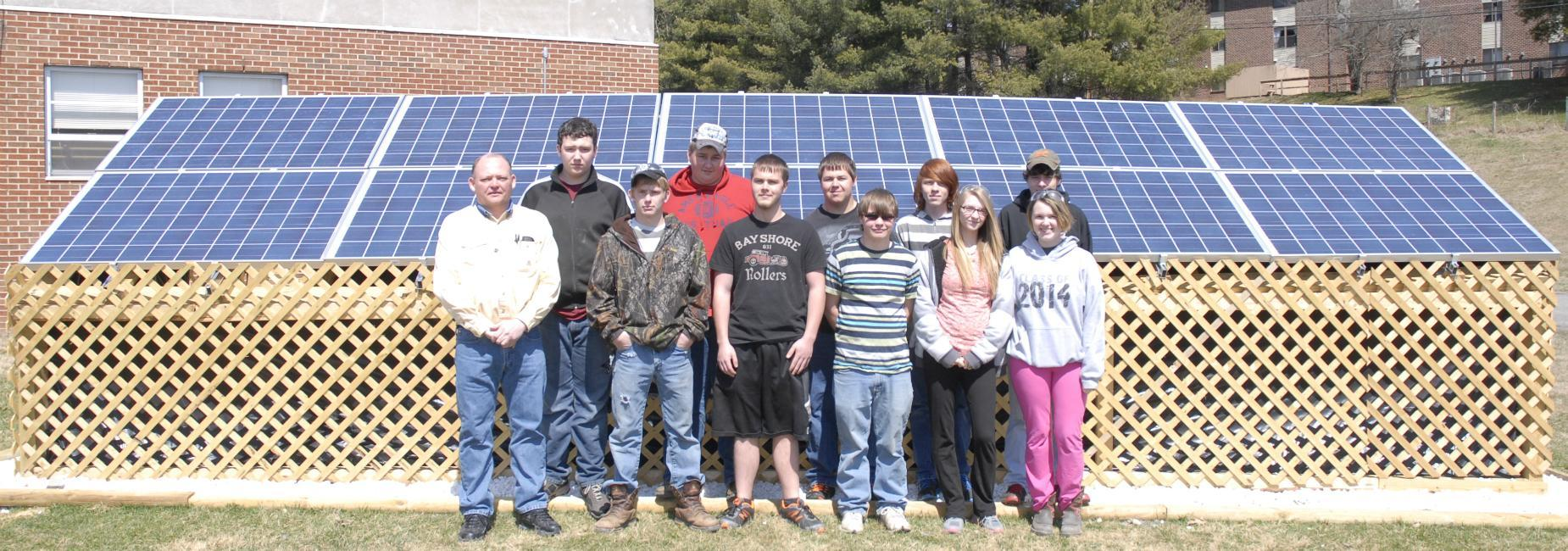Electronics/electricity students posing in front of Career Center's solar panel array
