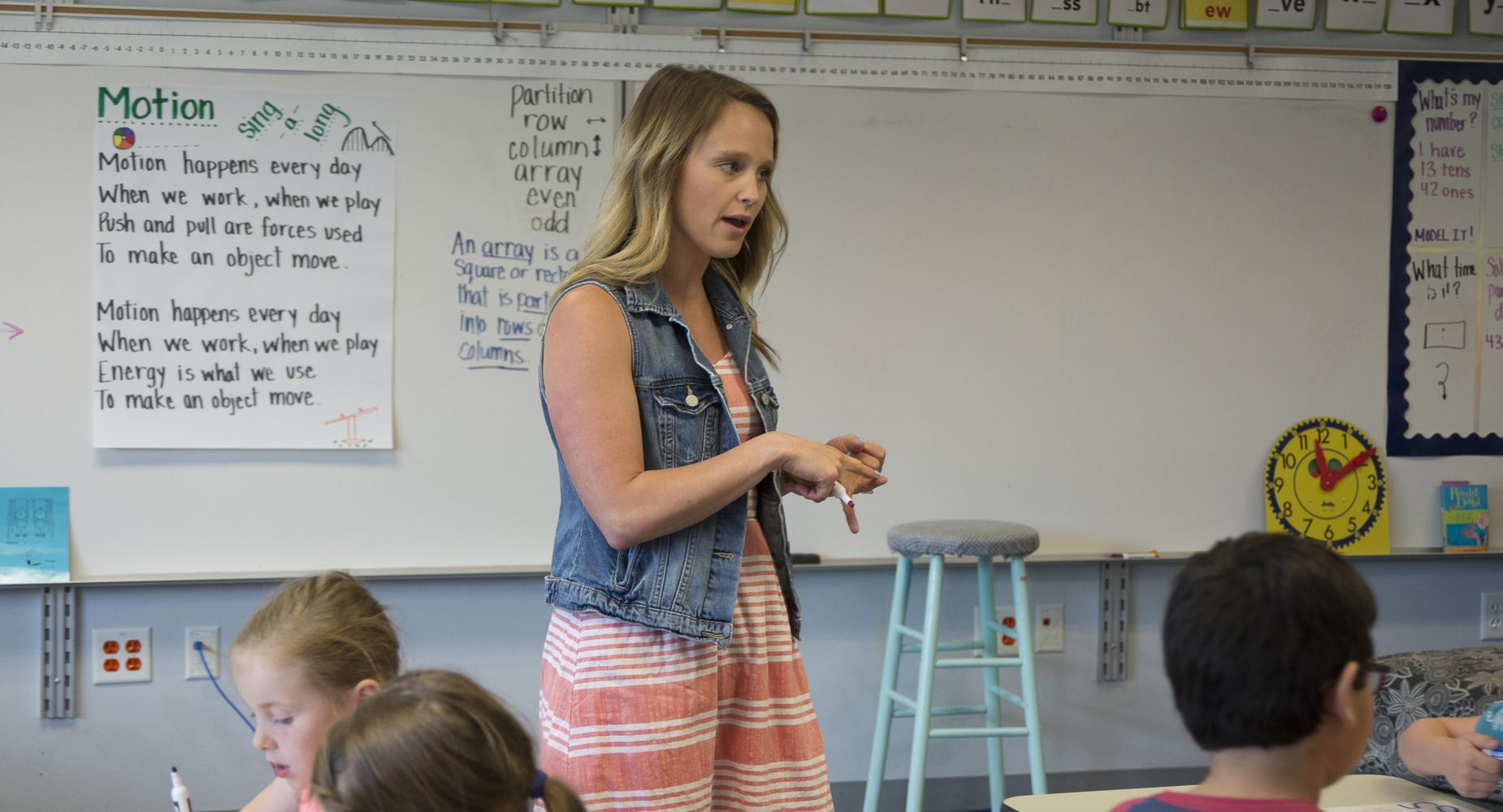 Teacher talks with kids from front of classroom
