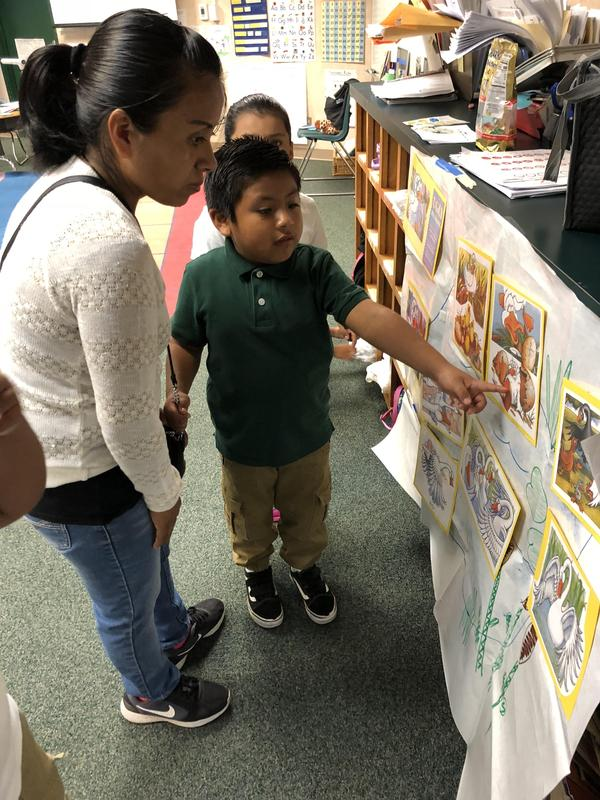 A child sharing their poster with their parent