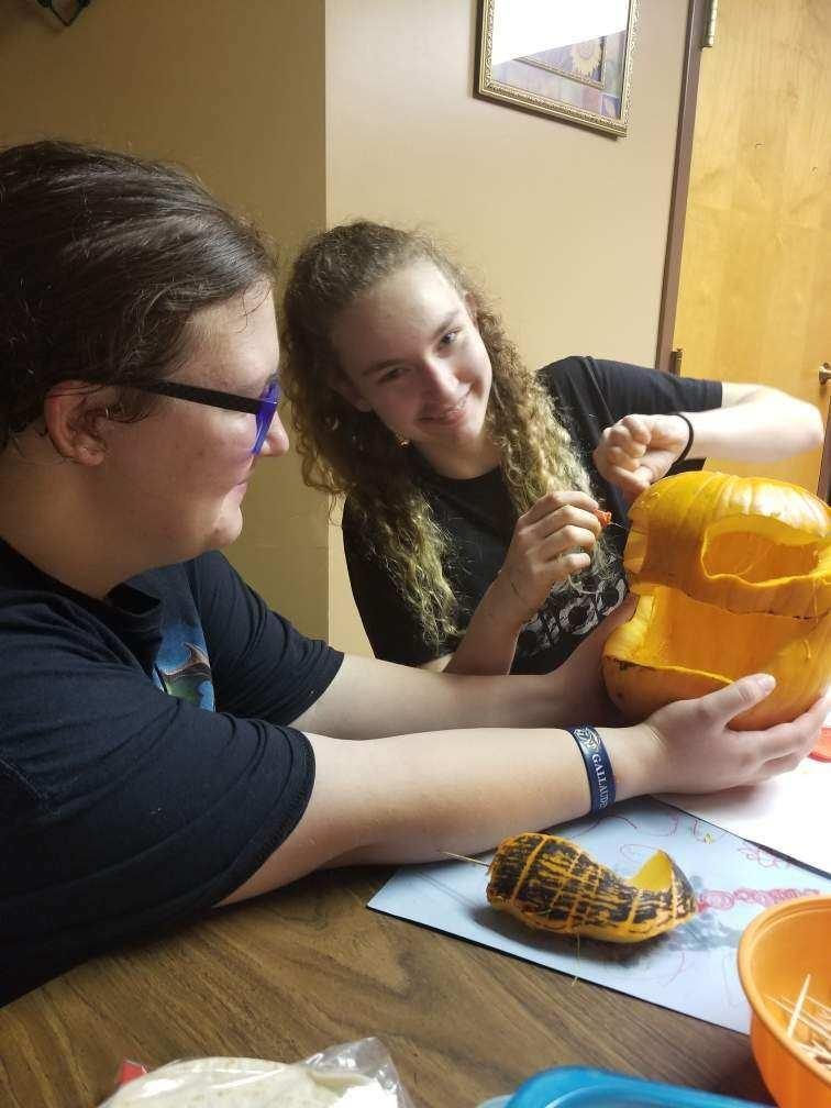 Two students carving a pumpkin together