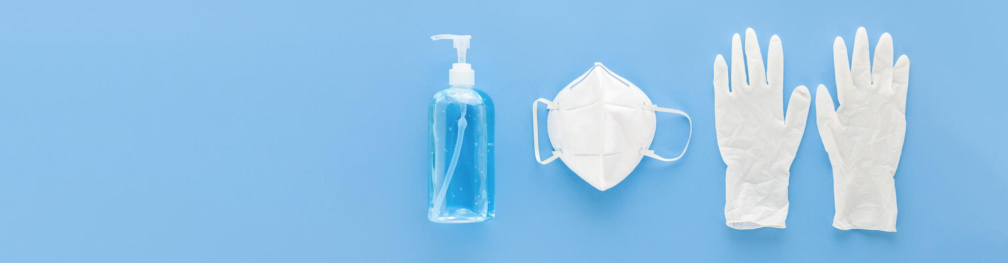 Hand sanitize and a mask against a blue background