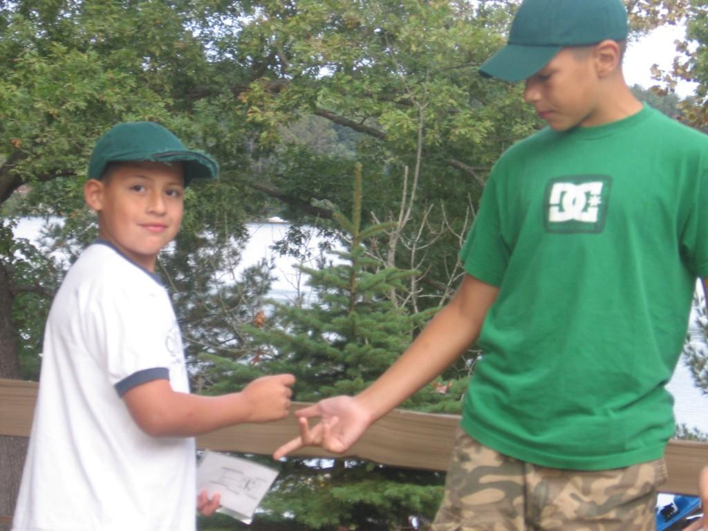 two boys prepare to shake hands on deck overlooking lake