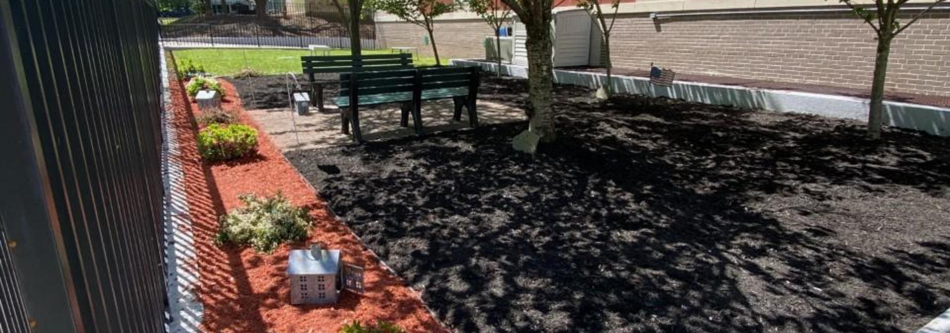 Reading garden with green benches, bushes and orange mulch