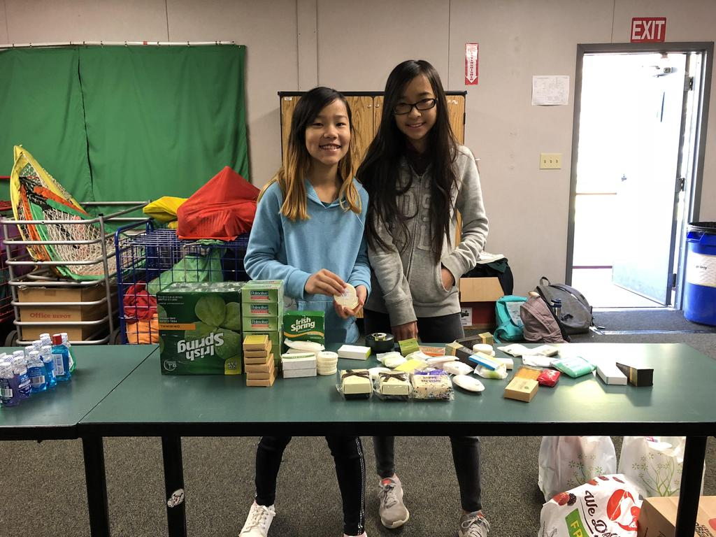 Two CCA students standing behind a table full of toiletries.
