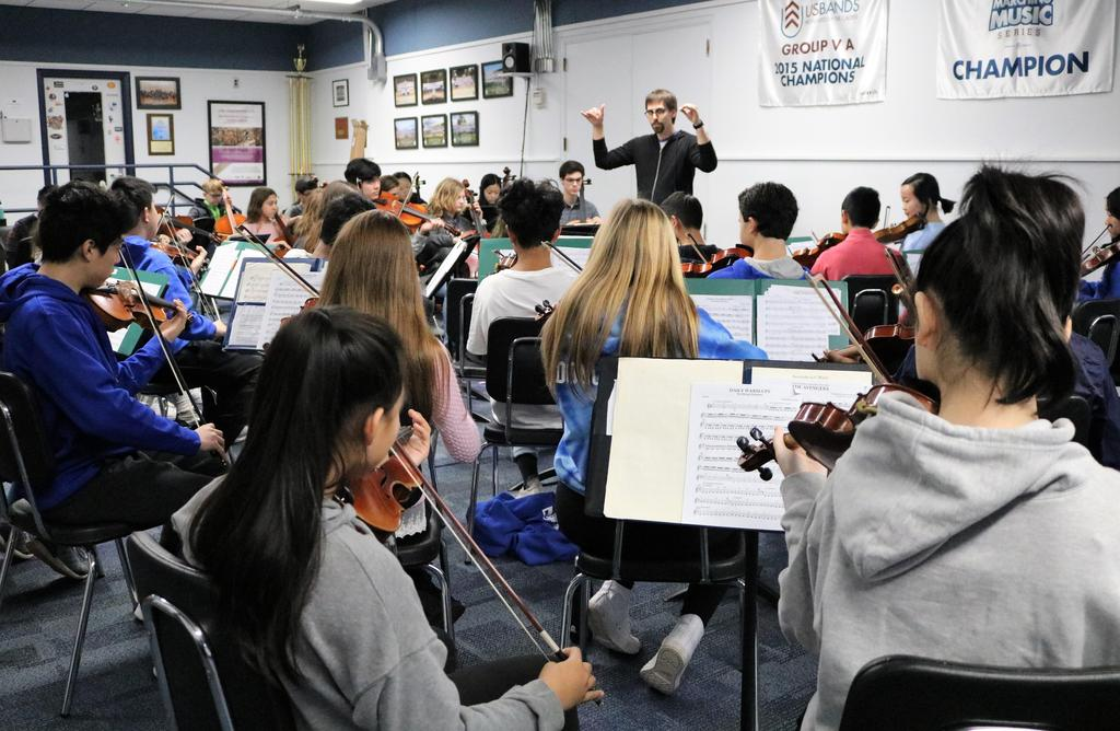 Photo of WHS orchestra director working with high school and intermediate school student musicians during District Music Day.