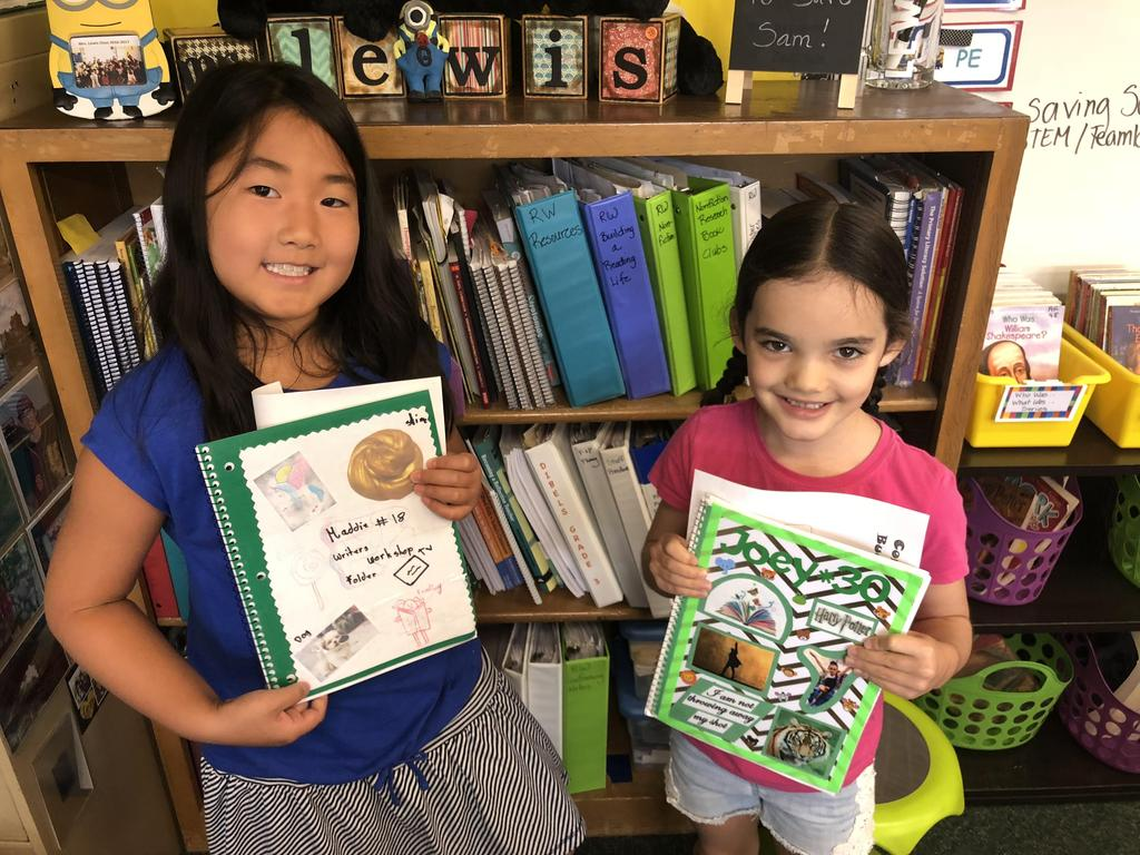 Two girls sharing their writer's notebooks.