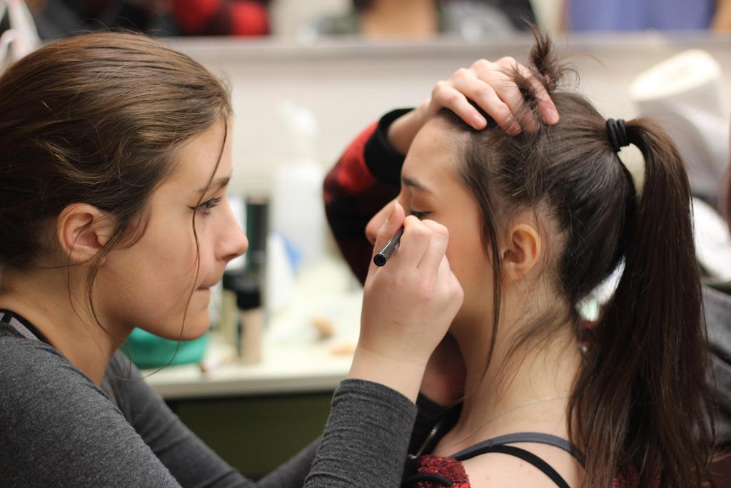 One student applying eye makeup on another student