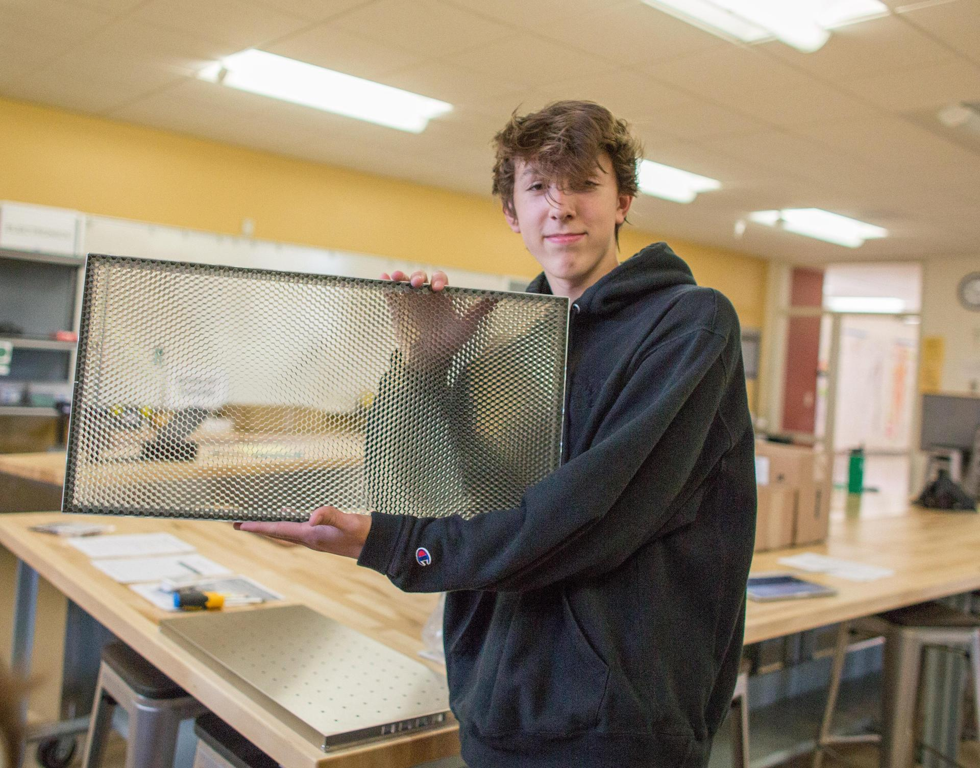 student holding up piece of glass
